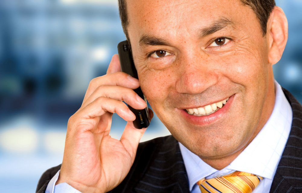 Business man on the phone in an office over a blue background